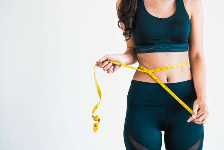 femme au corps mince mesurant sa taille