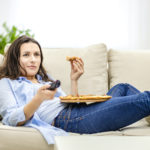femme grignotant à la maison devant la télé dans son canapé